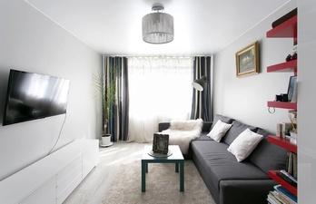 Светлая гостиная с большим диваном и телевизором