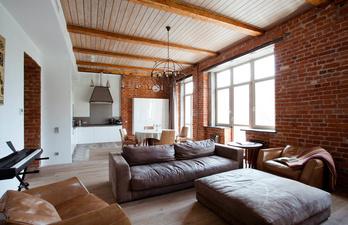 Гостиная с кирпичной стеной и балками на потолке