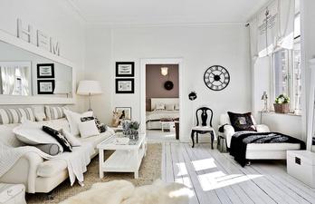 Белая комната с зеркалом над белым диваном