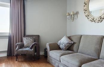 Гостиная с диваном и красивым креслом у окна