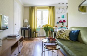 Гостиная с зеркалом над зелёным диваном