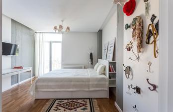 Спальня с белыми стенами и телевизором